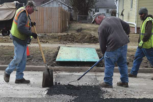 Jacksonville Street Department employees Earl McMeans (from left) and Dean Turner work to repair South Kosciusko Street.