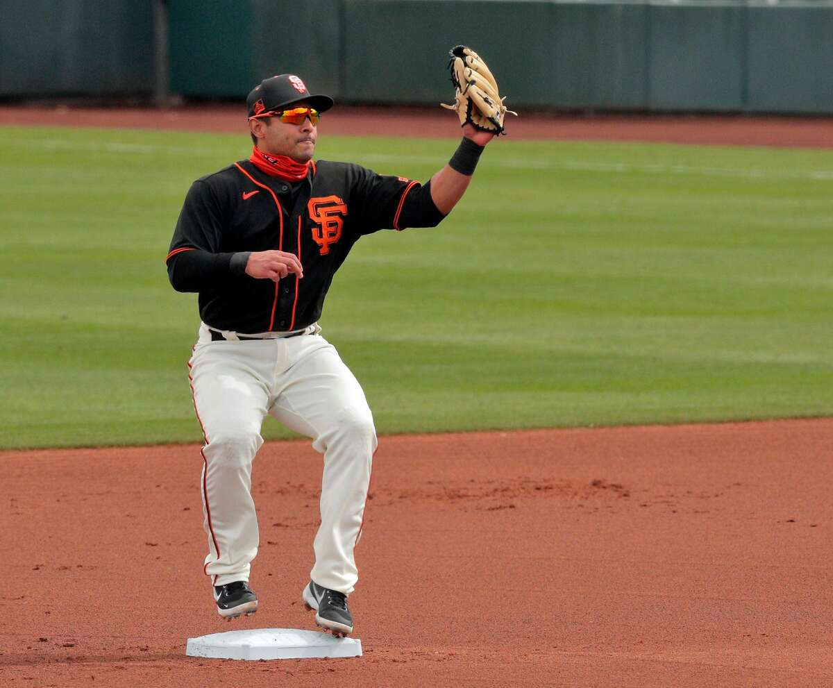 Donovan Solano (7) steps on the bag to start an inning-ending double play in the first inning as the San Francisco Giants played the Los Angeles Angels at Scottsdale Stadium in Scottsdale, Ariz., on Sunday, February 28, 2021.