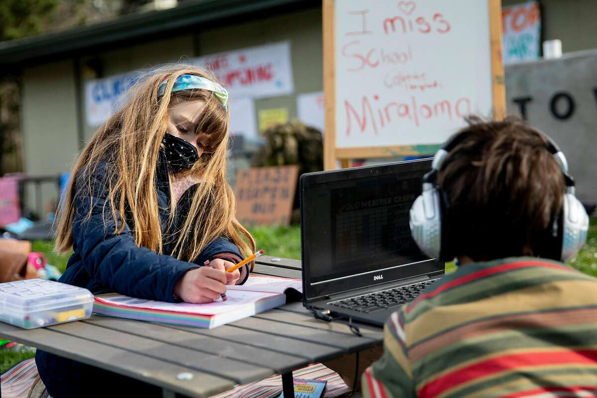 """Miraloma first-grader Colette Schwab, 6, works on homework for her remote class at Midtown Terrace Park in San Francisco in a """"Zoom in"""" demonstration with fellow students."""