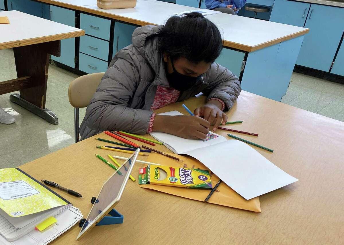 Shelton High School freshman Nicole Zitnay works on her artwork.