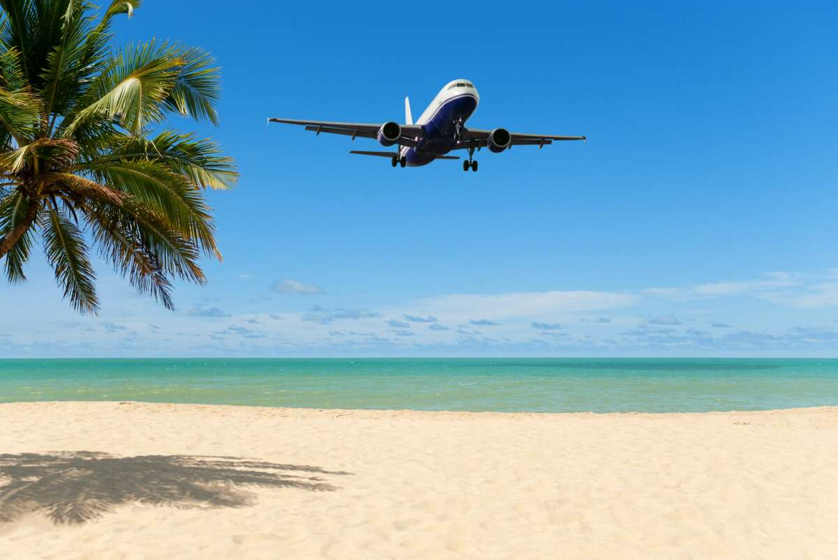 Airplane arriving at a tropical beach holiday resort, showing white sandy beach, green ocean, blue sky and a coconut palm tree
