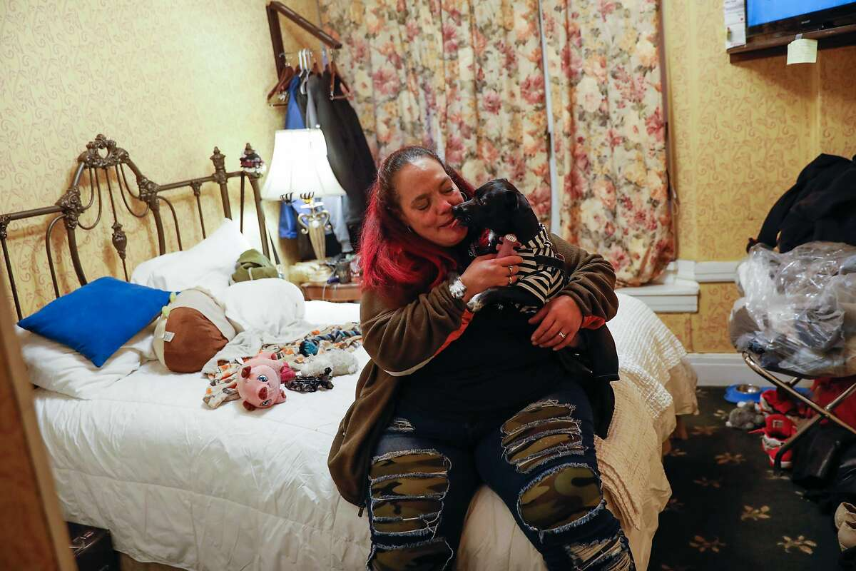 Chucky Torres embraces her dog, Yoda, in her hotel room in the Tenderloin. Chucky was previously homeless and hoping to get permanent housing.