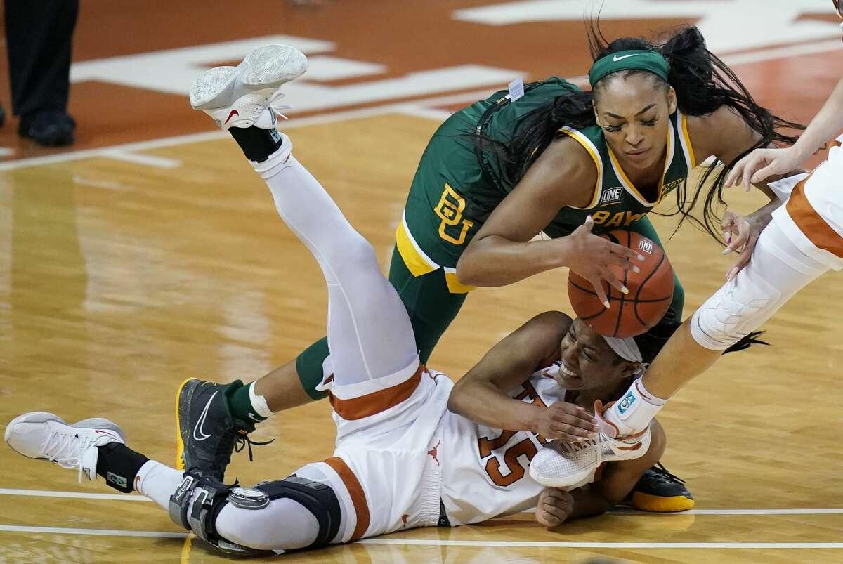 Baylor guard DiJonai Carrington, top, and Texas guard Kyra Lambert (15) scramble for a loose ball during the second half of an NCAA college basketball game, Monday, March 1, 2021, in Austin, Texas. (AP Photo/Eric Gay)