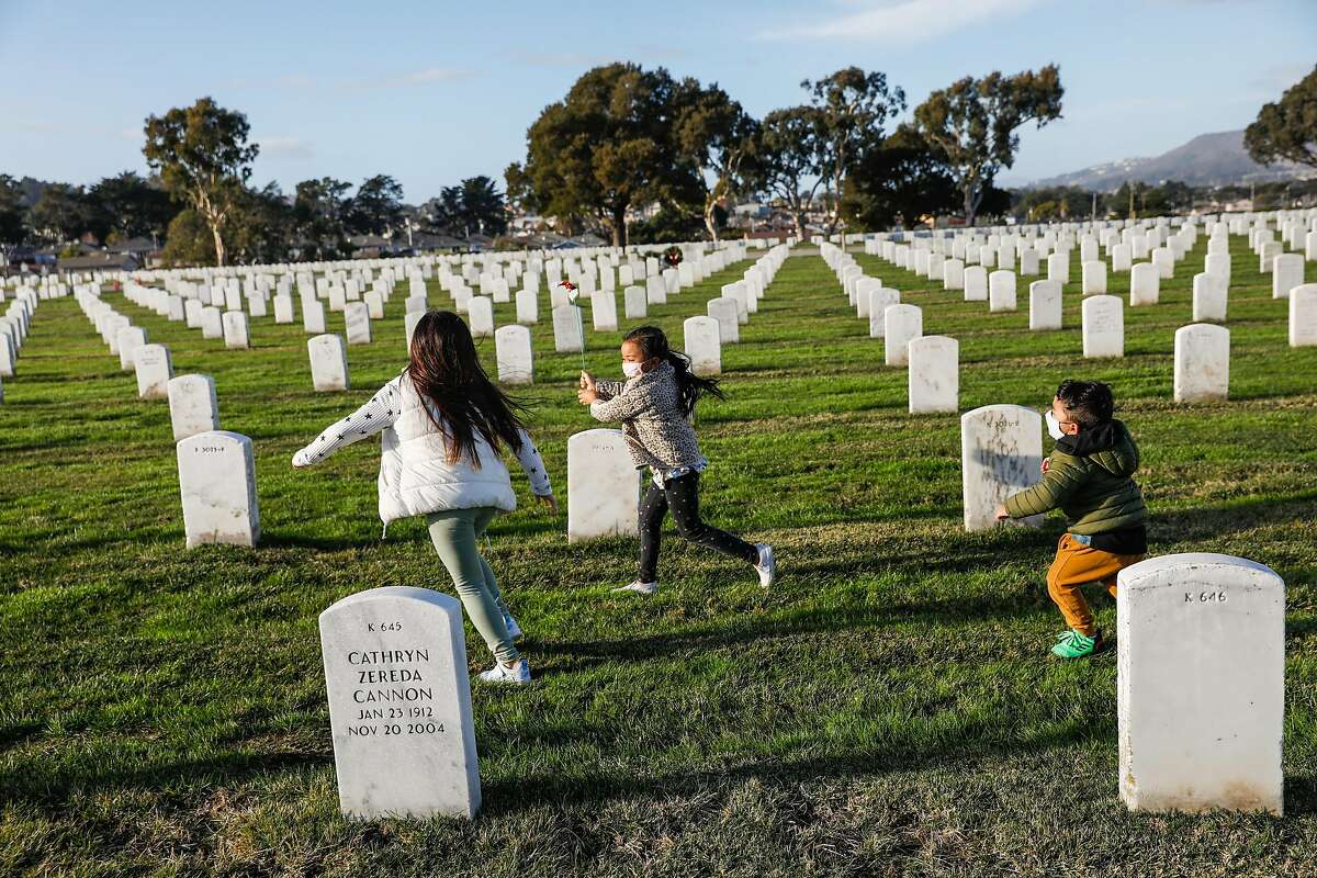 Taya, 8, Marz 6, and Derek, 3, play in the cemetery where their grandfather Jesus Baluyot, who died of COVID-19, is buried on Dec. 17 in San Bruno.