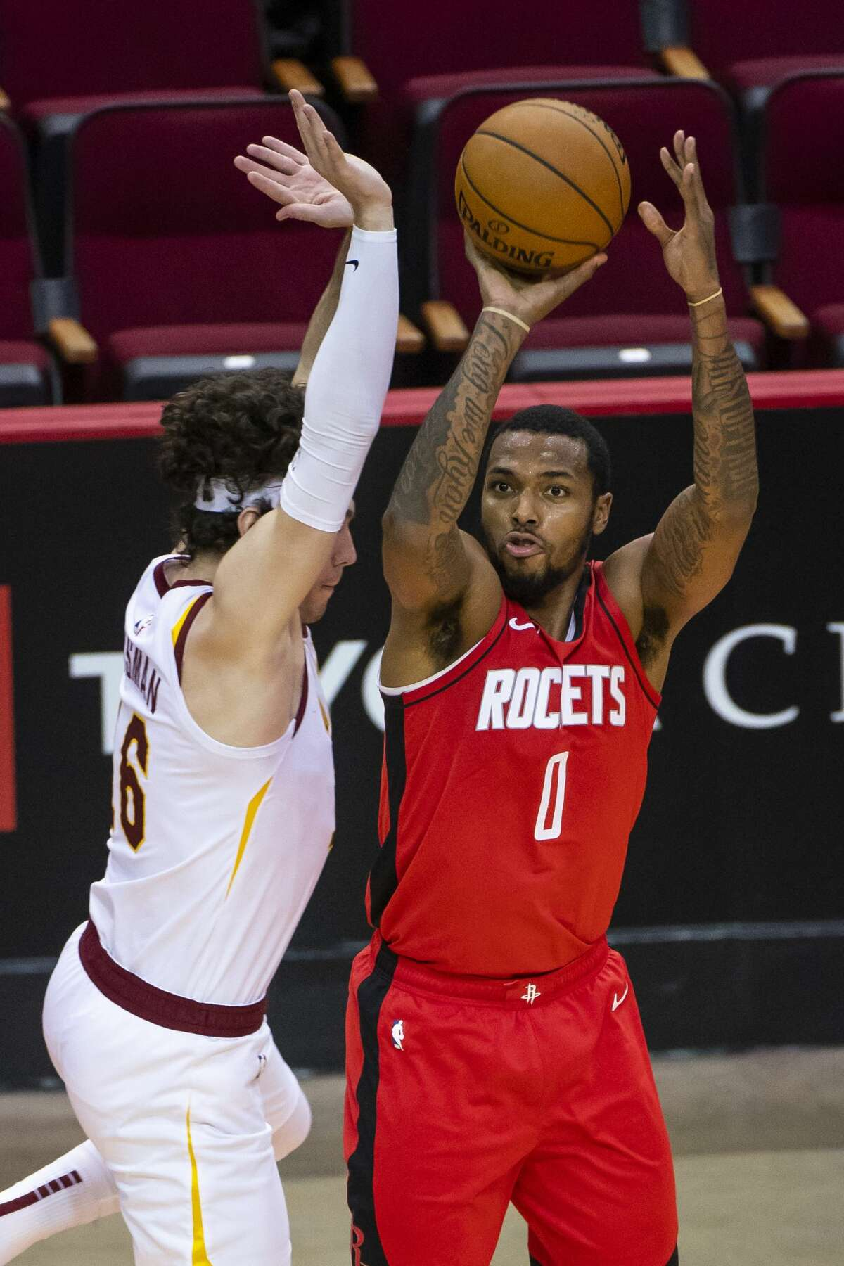 Houston Rockets guard Sterling Brown (0) shoots a three point shot defended by Cleveland Cavaliers forward Cedi Osman (16) during the third quarter of an NBA basketball game between the Houston Rockets and Cleveland Cavaliers on Monday, March 1, 2021, at Toyota Center in Houston.