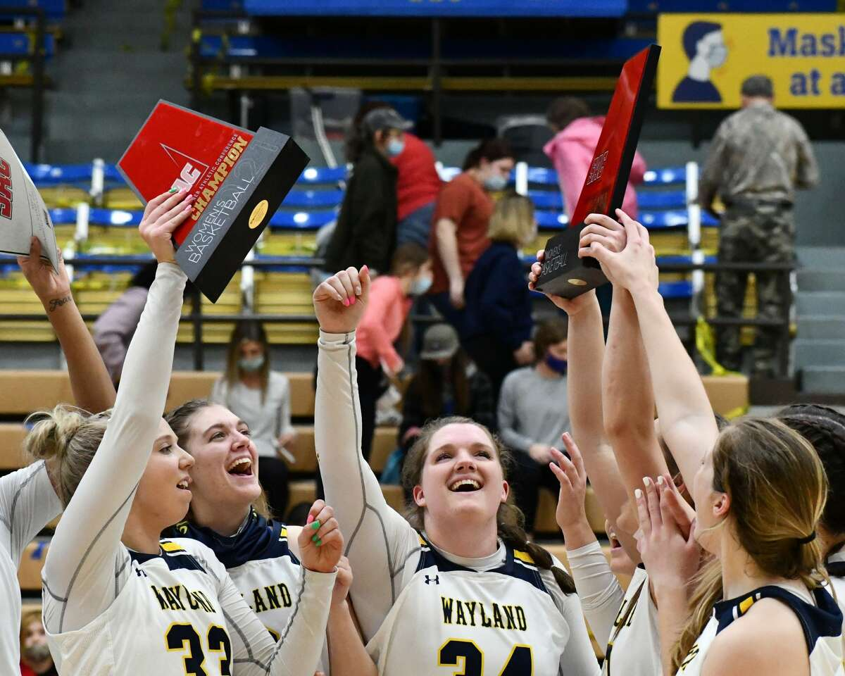 Members of the Wayland Baptist Flying Queens hold up the Sooner Athletic Conference regular-season and tournament championship trophies on Monday in the Hutcherson Center.