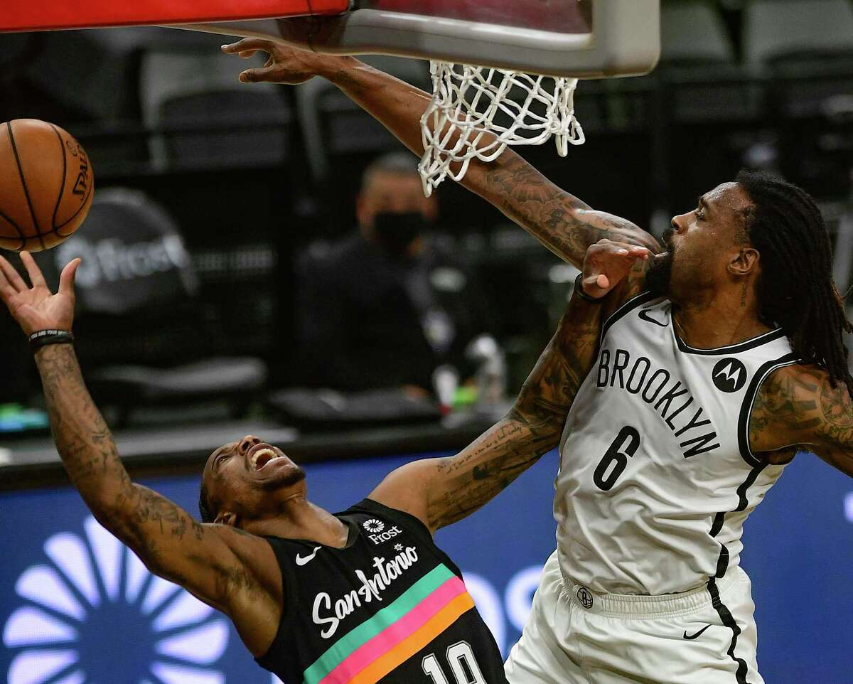 DeAndre Jordan (6) of the Brooklyn Nets plays a tough defense as DeMar DeRozan (10) of the San Antonio Spurs attempts a layup during NBA action in the AT&T Center on Monday, March 1, 2021.