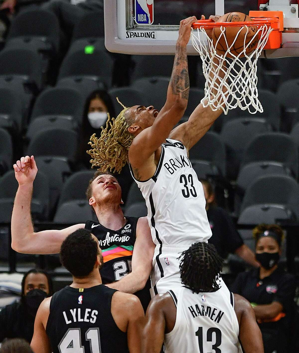 Nicolas Claxton (33) of the Brooklyn Nets dunks over Jakob Poeltl of the San Antonio Spurs during first-half NBA action in the AT&T Center on Monday, March 1, 2021.