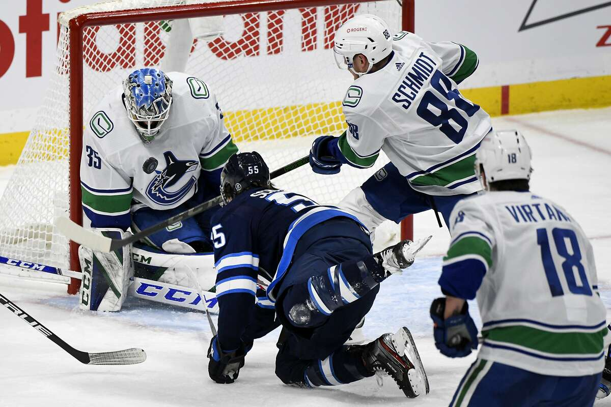 Vancouver Canucks goaltender Thatcher Demko (35) makes a save against Winnipeg Jets' Mark Scheifele (55) as Canucks' Nate Schmindt (88) defends during third-period NHL hockey game action in Winnipeg, Manitoba, Monday March 1, 2021. (Fred Greenslade/The Canadian Press via AP)