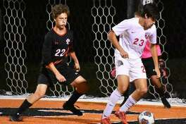 Edwardsville defender Andrew Mills, left, applies pressure on an Alton player late in the first half in Edwardsville last season. Mills will return this year for the Tigers.