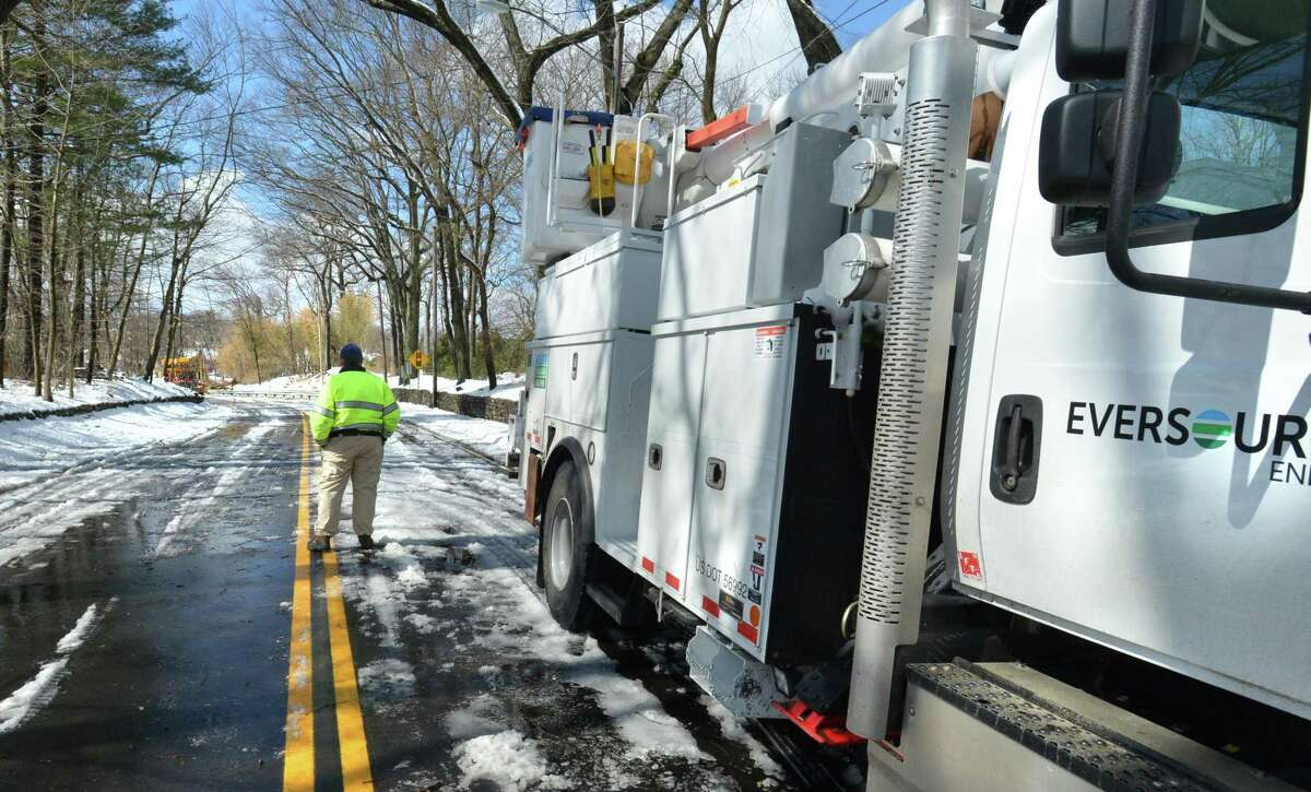 A Westport Police Officer stands at an Eversource truck as crews clear a fallen tree on Bridge St. that closed the road and the William F. Cribari Bridge over the Saugatuck River on Thursday March 8. 2018 in Westport Conn.
