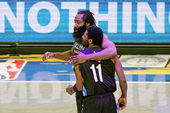 Brooklyn Nets guard James Harden (13) embraces guard Kyrie Irving (11) after Irving scored on a play during the second quarter of an NBA basketball game against the Orlando Magic, Thursday, Feb. 25, 2021, in New York. (AP Photo/Kathy Willens)