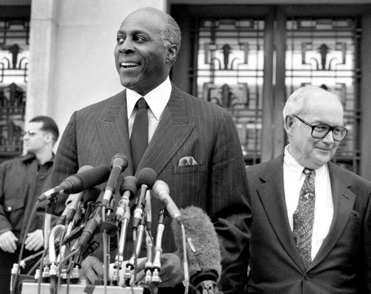 Vernon Jordan, left, a confidant of President Bill Clinton's, exits a courthouse in Washington, D.C., after testifying before a grand jury in 1998.