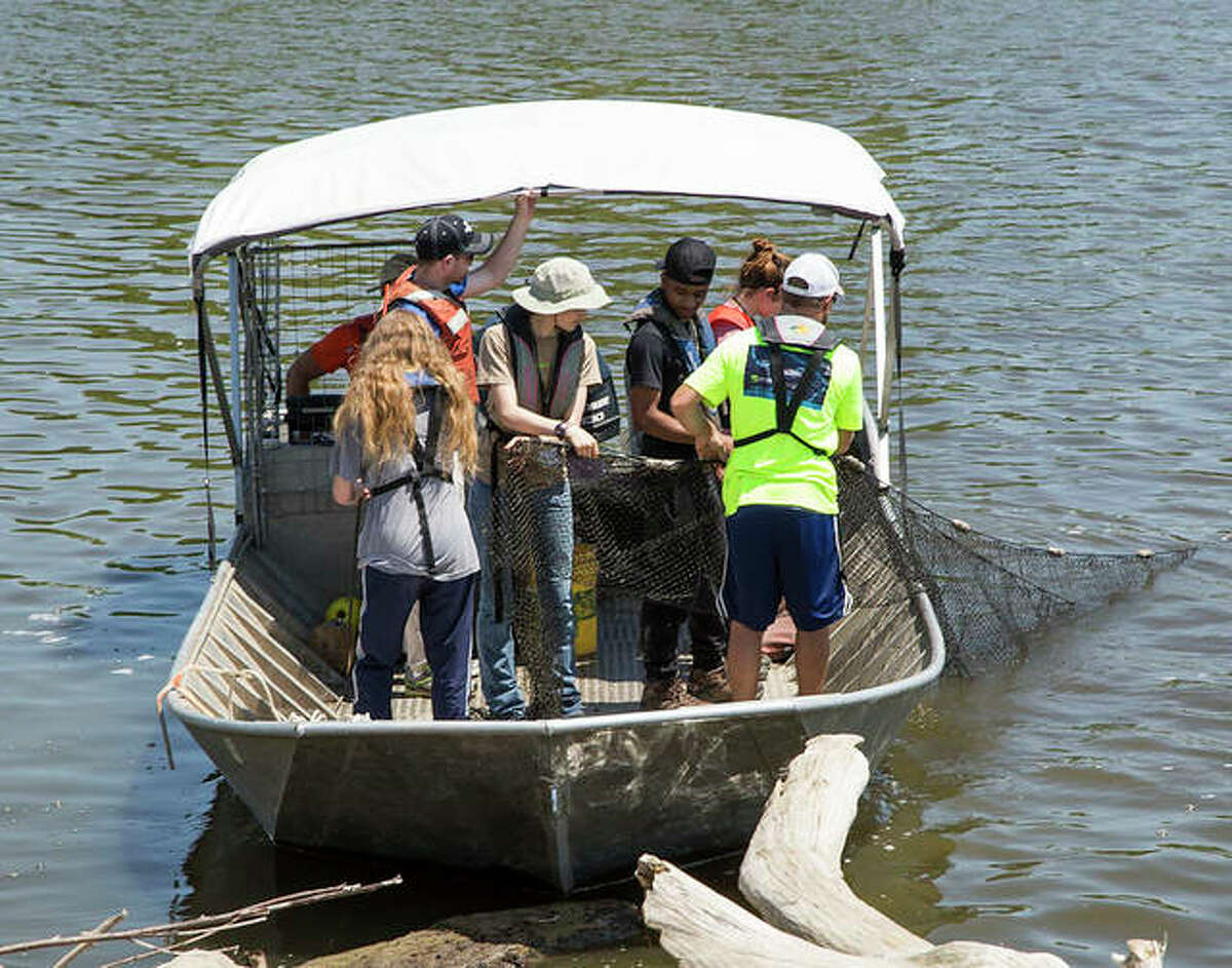 Previous NGRREC summer interns use a large fishing net to study aquatic life along the banks of the Mississippi River.