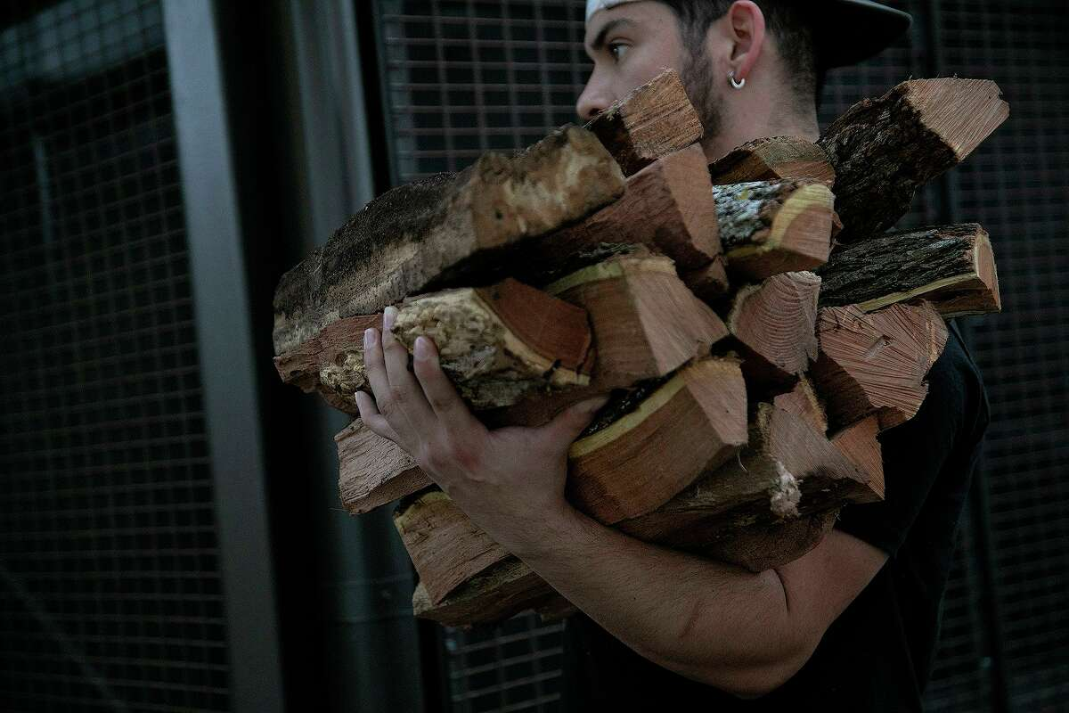 Just after the polar vortex, Gilbert Cantu carries oak wood for the barbecue pits at Pinkerton's Barbecue in downtown San Antonio. The Houston location's wood supplies were dicey during the storm.