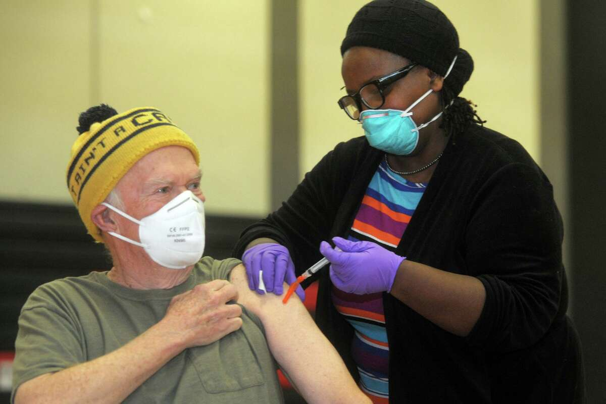 Bob Coogan, of Wilton, receives a shot of COVID-19 vaccine from nurse Martine Bristhole at a Bridgeport vaccination clinic set up in the gymnasium of Central High School in January of this year.