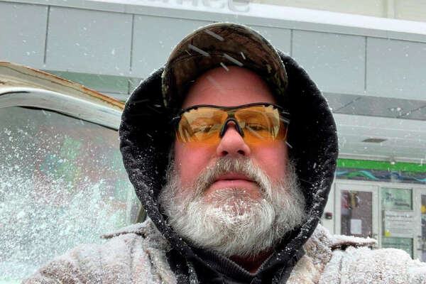 Kris Heeter is pictured covered in snow after clearing the sidewalk in front of Artworks. As well as plowing residential driveways, he helps keep paths in front of local businesses cleaned up and ready for customers.
