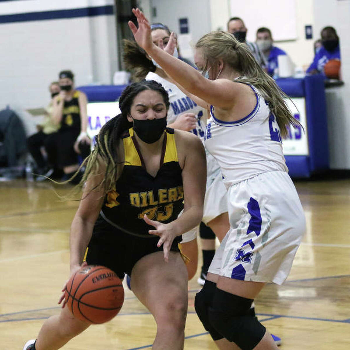 EA-WR's Emily Johnson (left) drives on a Marquette Catholic defender in a game earlier this season. Johnson, a freshman, had 14 points and 10 rebounds in the Oilers win Monday in Wood River.