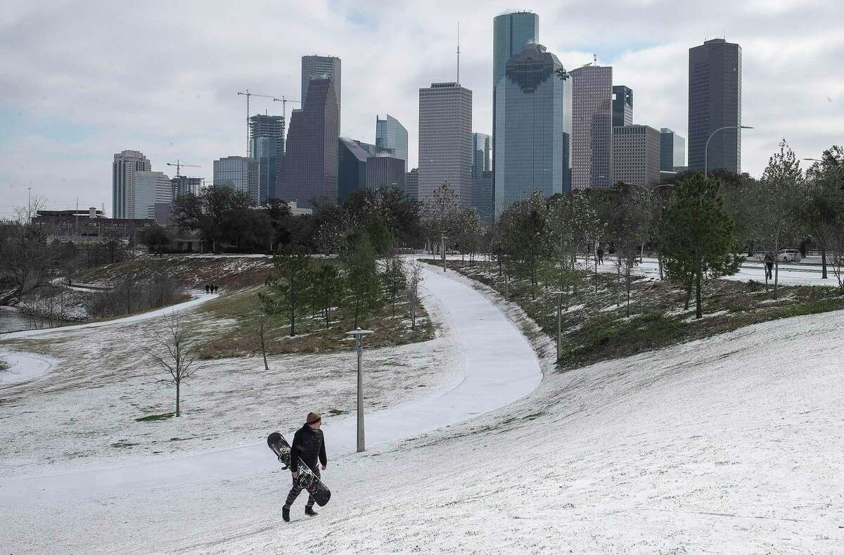 """Greg Gangluff carries his snowboard up a hill after riding it down as a winter storm hits Houston on Monday, Feb. 15, 2021, at Buffalo Bayou Park in Houston. """"We'll see if we can do it,"""" he said."""