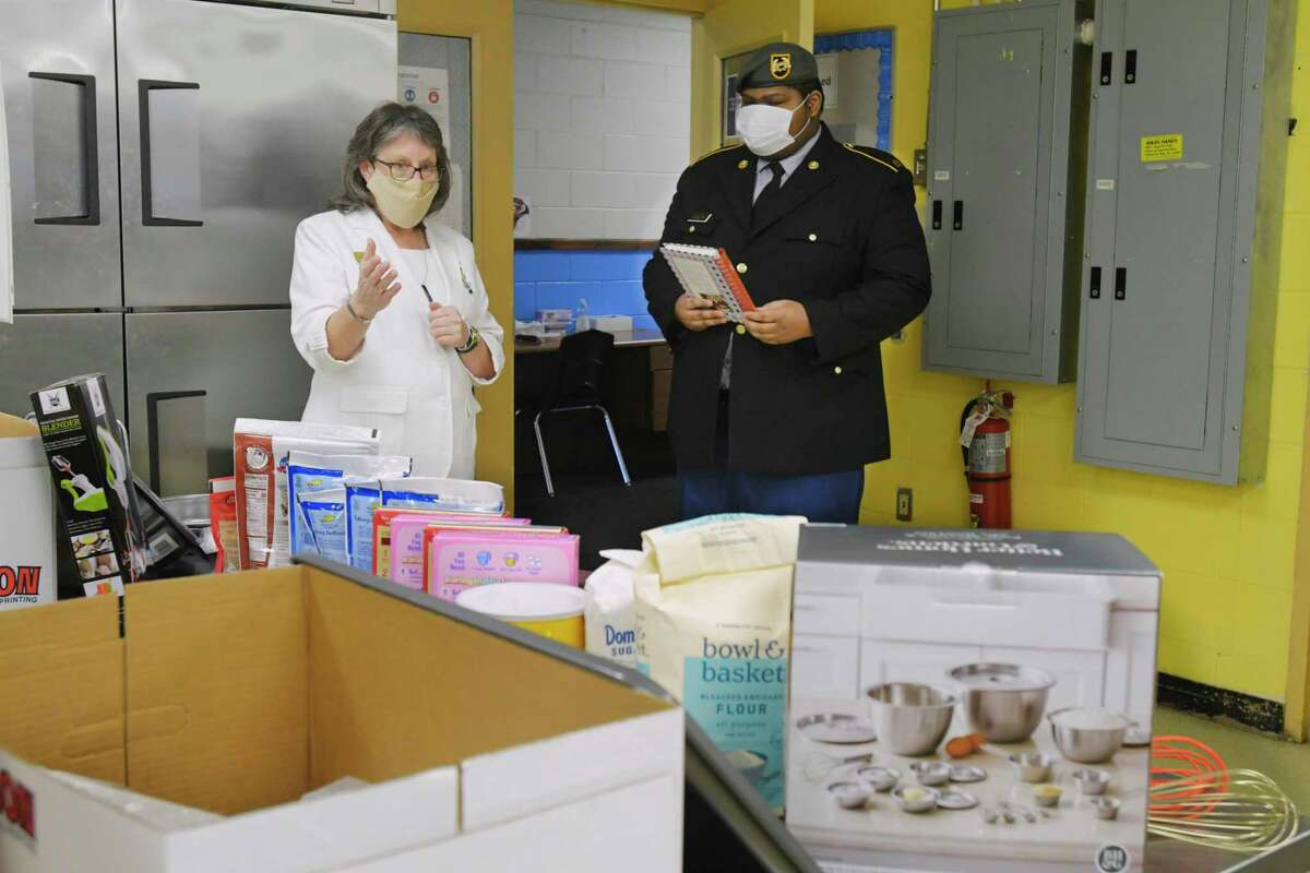 Carrie Farley, left, a member of the American Gold Star Mothers, Albany Chapter, presents Troy Millin, a member of the Sgt. Henry Johnson Battalion, Albany High School JROTC, with baking supplies at the Albany High School's Abrookin Career and Technical Center on Tuesday, March 2, 2021, in Albany, N.Y. Millin has started making cakes for local veterans to celebrate their birthdays. (Paul Buckowski/Times Union)