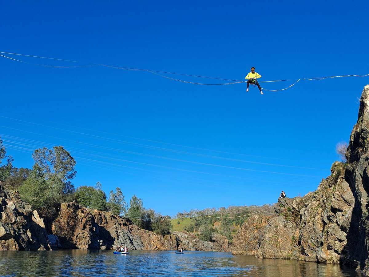 A group of slackliners are seen walking across a river in Folsom on February 28, 2021.