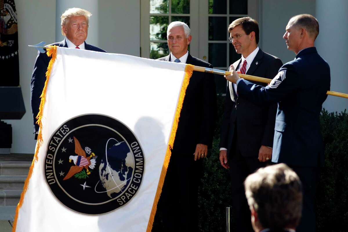 President Donald Trump, left, watches with Vice President Mike Pence and Defense Secretary Mark Esper as the flag for U.S. space Command is unfurled as Trump announces the establishment of the U.S. Space Command in the Rose Garden of the White House in Washington. The Department of the Defense Inspector General on Friday, Feb. 19, 2021, has announced an investigation into the Trump administration's January decision to move the U.S. Space Command headquarters from Peterson Air Force Base in Colorado to the Redstone Arsenal adjacent to Huntsville, Ala. The announcement follows protests by Colorado's congressional delegation that the decision was politically motivated.