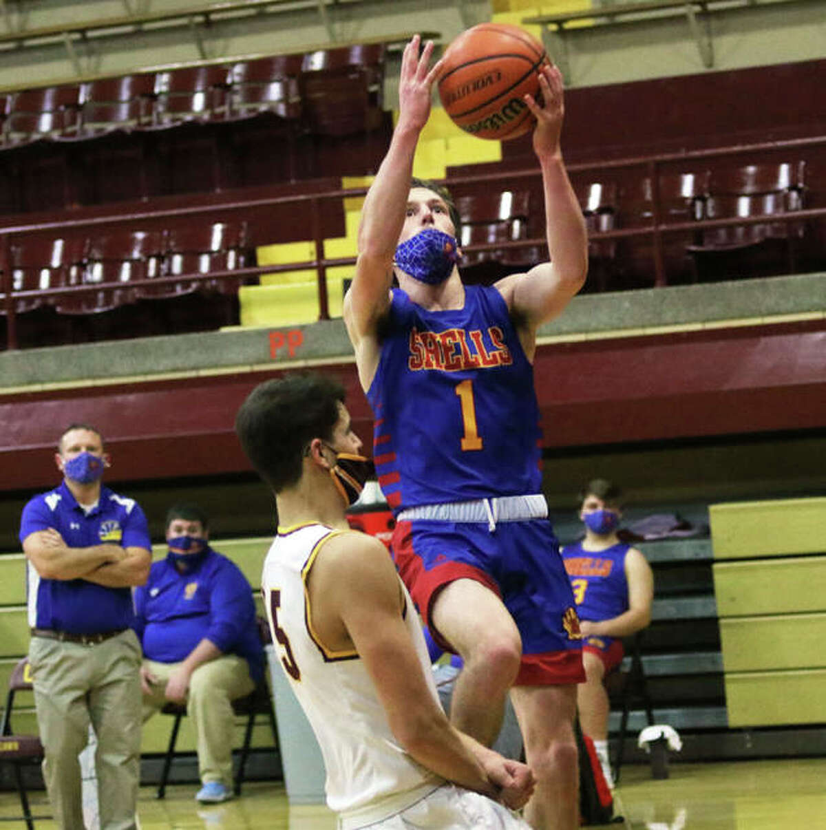 Roxana senior Drew Beckman (1) does in for a layup past EA-WR's Ryan Dawson in a Feb. 6 game in Wood River. Beckman has been dismissed from the team shortly after becoming the 12th player in program history to score 1,000 career points.