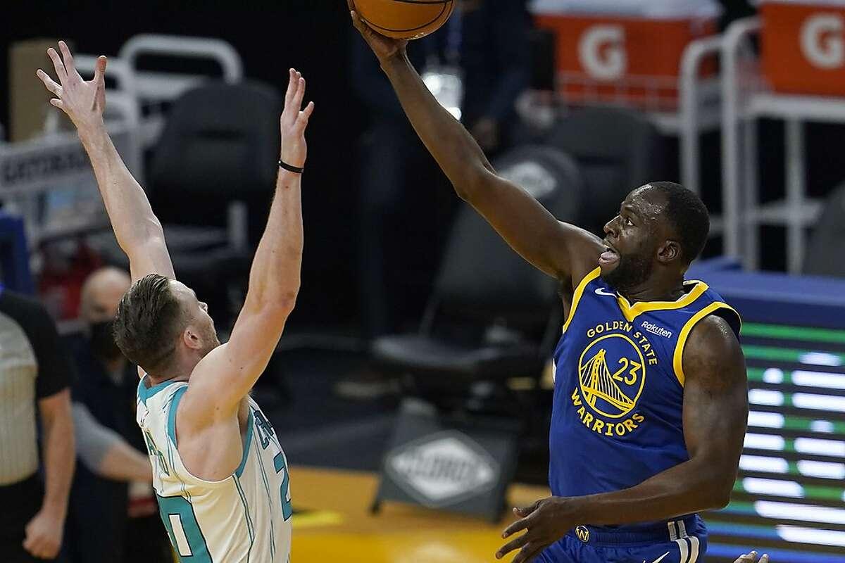 Golden State Warriors forward Draymond Green shoots against Charlotte Hornets forward Gordon Hayward during the first half of a Feb. 26 game.