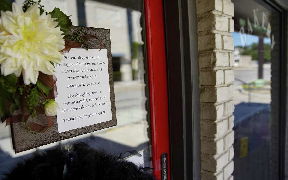 A person looks in the window of The Sugar Shop, a bakery in Bellaire, Texas, on Monday, Nov. 16, 2020. The bakery has closed after its owner, Nathan Maynor, 58, died of COVID after being diagnosed in October.