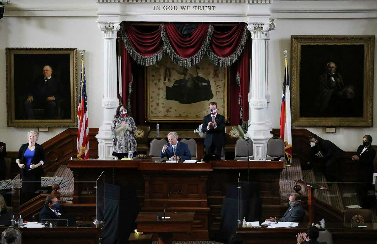 Texas Governor Greg Abbott (center) delivers a speech while his wife, Cecilia (left) and newly elected Speaker of the House, Dade Phelan (on right), join him during the convening of the 87th Texas Legislature in Austin on Tuesday, Jan. 12, 2021.