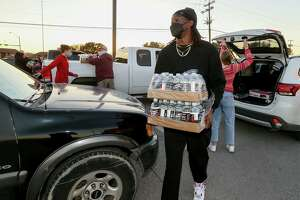 Seattle Seahawks cornerback and former Judson standout Tre Flowers distributes boxes of bottled water at a meal and water distribution at Rutledge Stadium on Feb. 20. Flowers, a 2013 Judson High School graduate who was selected by the Seattle Seahawks in the fifth round of the 2018 NFL Draft, assembled a team of volunteers to create the food and water distribution in Converse.