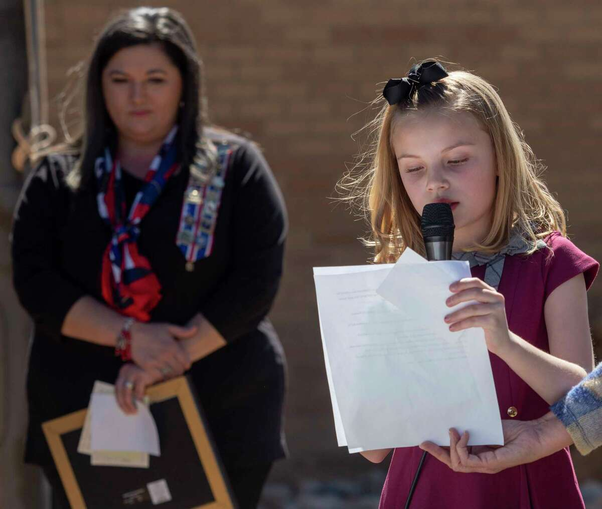 """Elizabeth Staley, fourth grader at Hillander School, reads her winning Texas history essay, """"Anson Jones. The Architect of Annexation"""" 03/02/2021, presented by Daughters of the Republic of Texas Aaron Estes Chapter, outside the Haley Library during the Texas Independence celebration. Tim Fischer/Reporter-Telegram"""