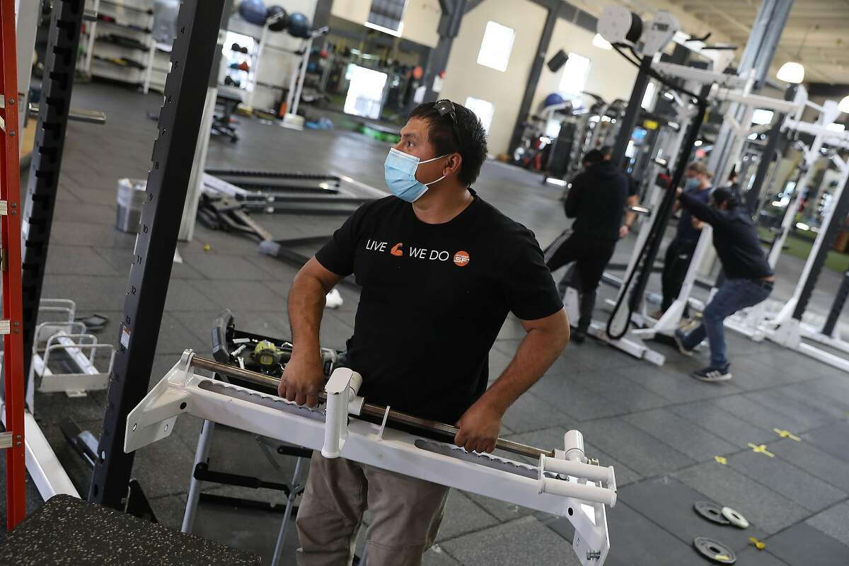 Sal Moscoso, laborer, reassembles exercise equipment at the indoor Fitness SF gym to prepare for the reopening of the indoor gym on Tuesday, March 2, 2021 in San Francisco.