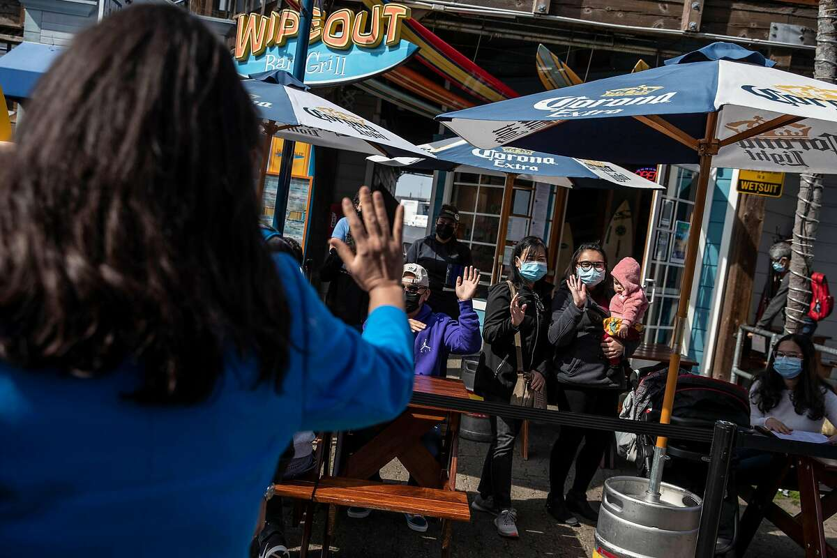 San Francisco Mayor London Breed waves to a group of visitors at the Wipeout Bar & Grill at Pier 39 on Mar. 2, 2021.