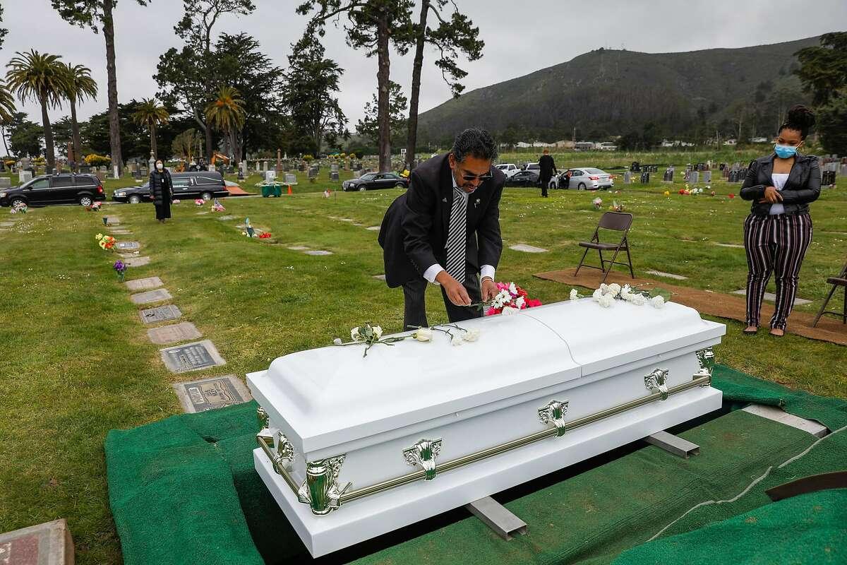 Funeral director Vaughn O. Nixon Sr. arranges the casket of COVID-19 victim Tessie Henry, 83, buried April 8 in Colma.