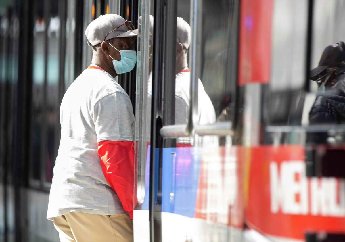 A passenger enters a Metropolitan Transit Authority Red Line train at the Main Street Square stop on Feb. 3, 2021, in downtown Houston. Despite state officials scaling back mask requirements in Texas, face coverings will continue to be required on Metro buses and trains.