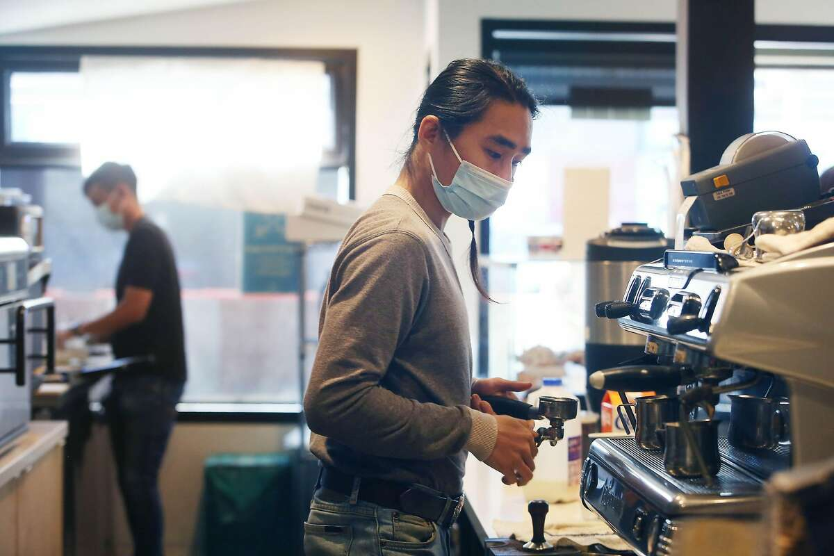 Kyle Lee (front), barista and Richie Woo (back), barista, prepare orders for customers at Henry's House of Coffee on Monday, March 1, 2021 in San Francisco, Calif.
