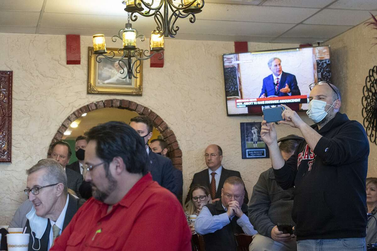 Texas Gov. Greg Abbott delivers an announcement rescinding a mask mandate and limits on businesses while a crowd watches him at Montelongo's Mexican Restaurant in Lubbock, Texas.