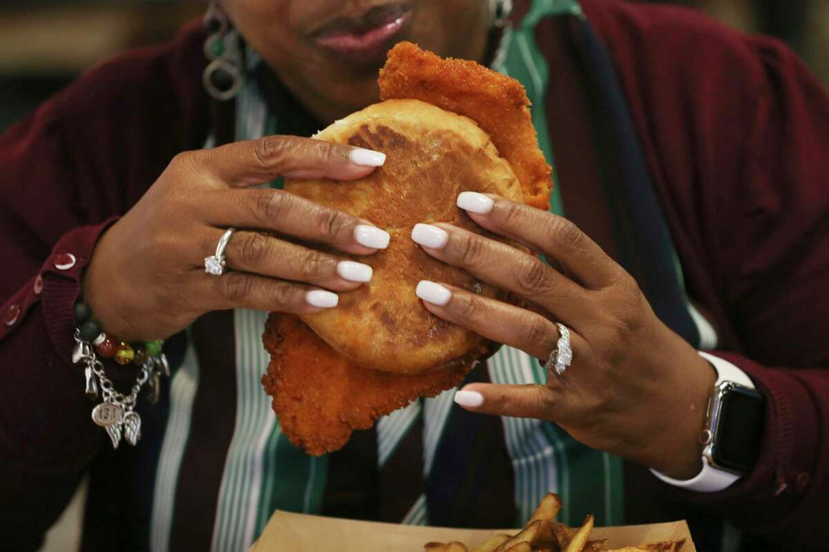 Yolanda Chance prepares to take a bite of the Nashville Hot chicken sandwich at Smack's Chicken Shack Monday.
