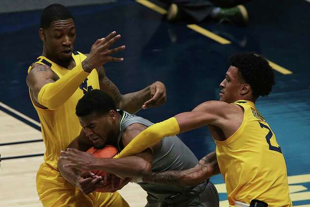 Baylor guard Jared Butler (12) is defended by West Virginia forwards Gabe Osabuohien (3) and Jalen Bridges (2) during the first half of an NCAA college basketball game Tuesday, March 2, 2021, in Morgantown, W.Va. (AP Photo/Kathleen Batten) Photo: Kathy Batten, Associated Press / Copyright 2021 The Associated Press. All rights reserved