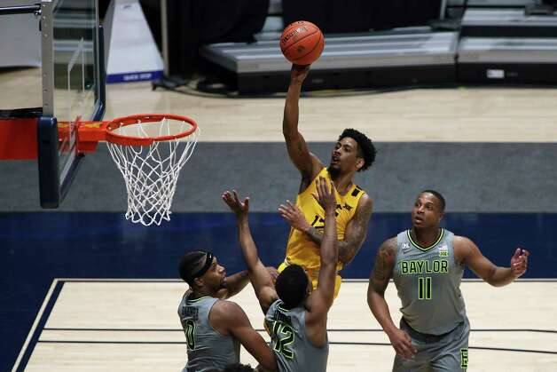 West Virginia guard Taz Sherman (12) shoots while defended by Baylor forward Flo Thamba (0) and guards Jared Butler (12) and Mark Vital (11) during the first half of an NCAA college basketball game Tuesday, March 2, 2021, in Morgantown, W.Va. (AP Photo/Kathleen Batten) Photo: Kathy Batten, Associated Press / Copyright 2021 The Associated Press. All rights reserved