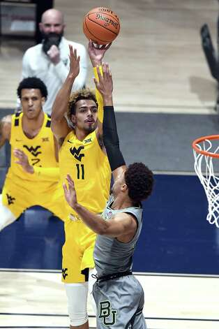 MORGANTOWN, WV - MARCH 02:  Emmitt Matthews Jr. #11 of the West Virginia Mountaineers takes a shot over over MaCio Teague #31 of the Baylor Bears in the first half during a college basketball game at WVU Coliseum  on March 2, 2021 in Morgantown, West Virginia. Photo: Mitchell Layton, Getty Images / 2021 Getty Images