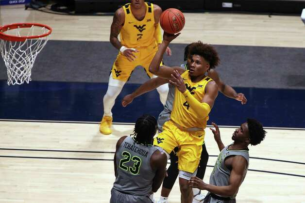 West Virginia guard Miles McBride (4) shoots while defended by Baylor forward Jonathan Tchamwa Tchatchoua (23) and guard Adam Flagler (10) during the first half of an NCAA college basketball game Tuesday, March 2, 2021, in Morgantown, W.Va. (AP Photo/Kathleen Batten) Photo: Kathy Batten, Associated Press / Copyright 2021 The Associated Press. All rights reserved
