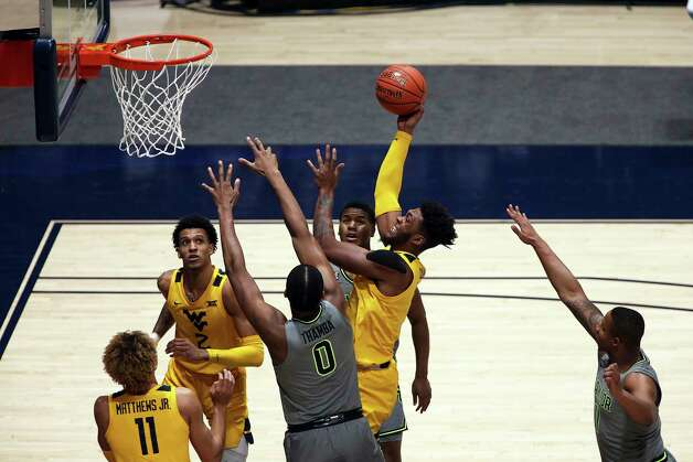 West Virginia forward Derek Culver (1) shoots while defended by Baylor forward Flo Thamba (0) and guard Jared Butler (12) during the first half of an NCAA college basketball game Tuesday, March 2, 2021, in Morgantown, W.Va. (AP Photo/Kathleen Batten) Photo: Kathy Batten, Associated Press / Copyright 2021 The Associated Press. All rights reserved