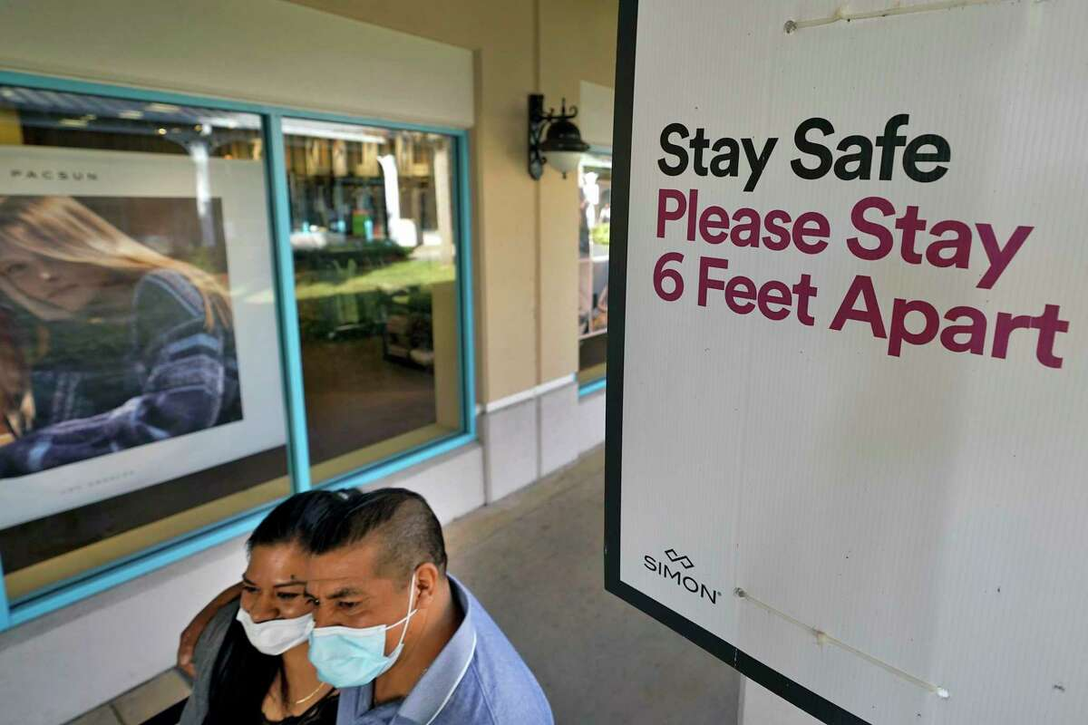 Shoppers wear protective face masks as they walk past a social distancing sign at the Ellenton Premium Outlet stores in Ellenton, Fla.