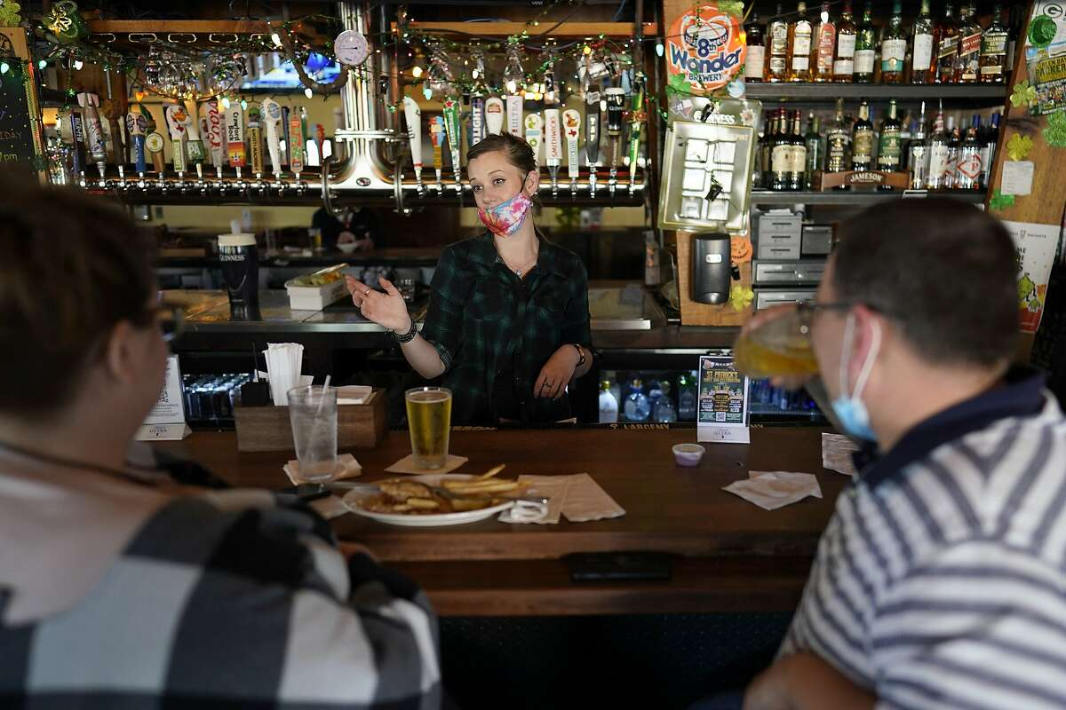Bartender Alyssa Dooley, center, talks with customers at Mo's Irish Pub, Tuesday, March 2, 2021, in Houston.