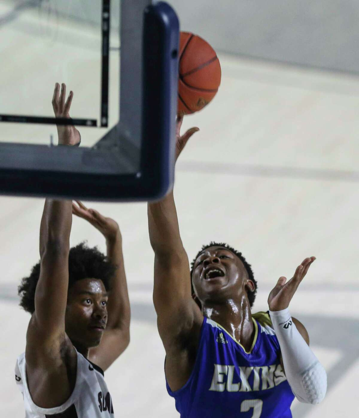 Elkins guard Jacolbi Harris (2) goes for a lay up while Summer Creek point guard Karter Dutton (11) is trying to stop him during the second quarter of a UIL 6A Region III Boys Basketball Playoffs Semifinal game Tuesday, March 2, 2021, at Delmar Fieldhouse in Houston.