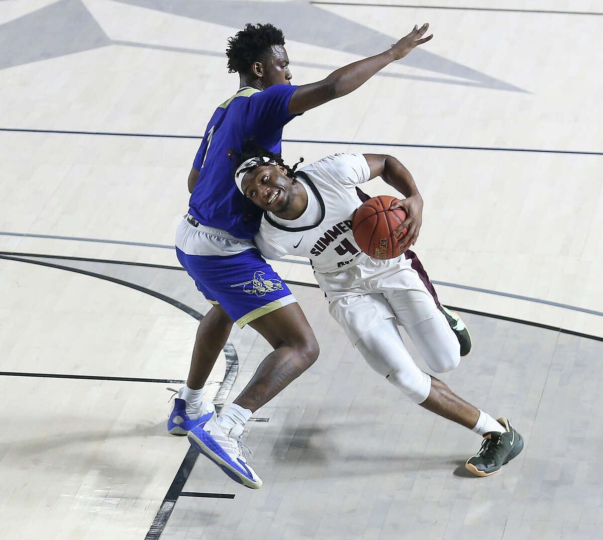 Summer Creek's Amaree Abram (4) is fouled by Elkins' Shane Bell (1) while dribbling toward the basket during the third quarter of a UIL 6A Region III Boys Basketball Playoffs Semifinal game Tuesday, March 2, 2021, at Delmar Fieldhouse in Houston.