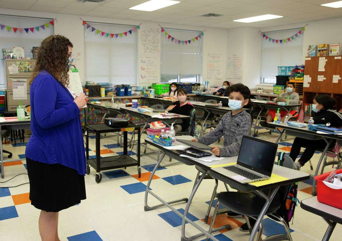 Hillary Smith, a fourth grade teacher at James DeAnda Elementary School, sets out a laptop to teach both in-person and virtally Tuesday, Feb. 9, 2021, in Houston.