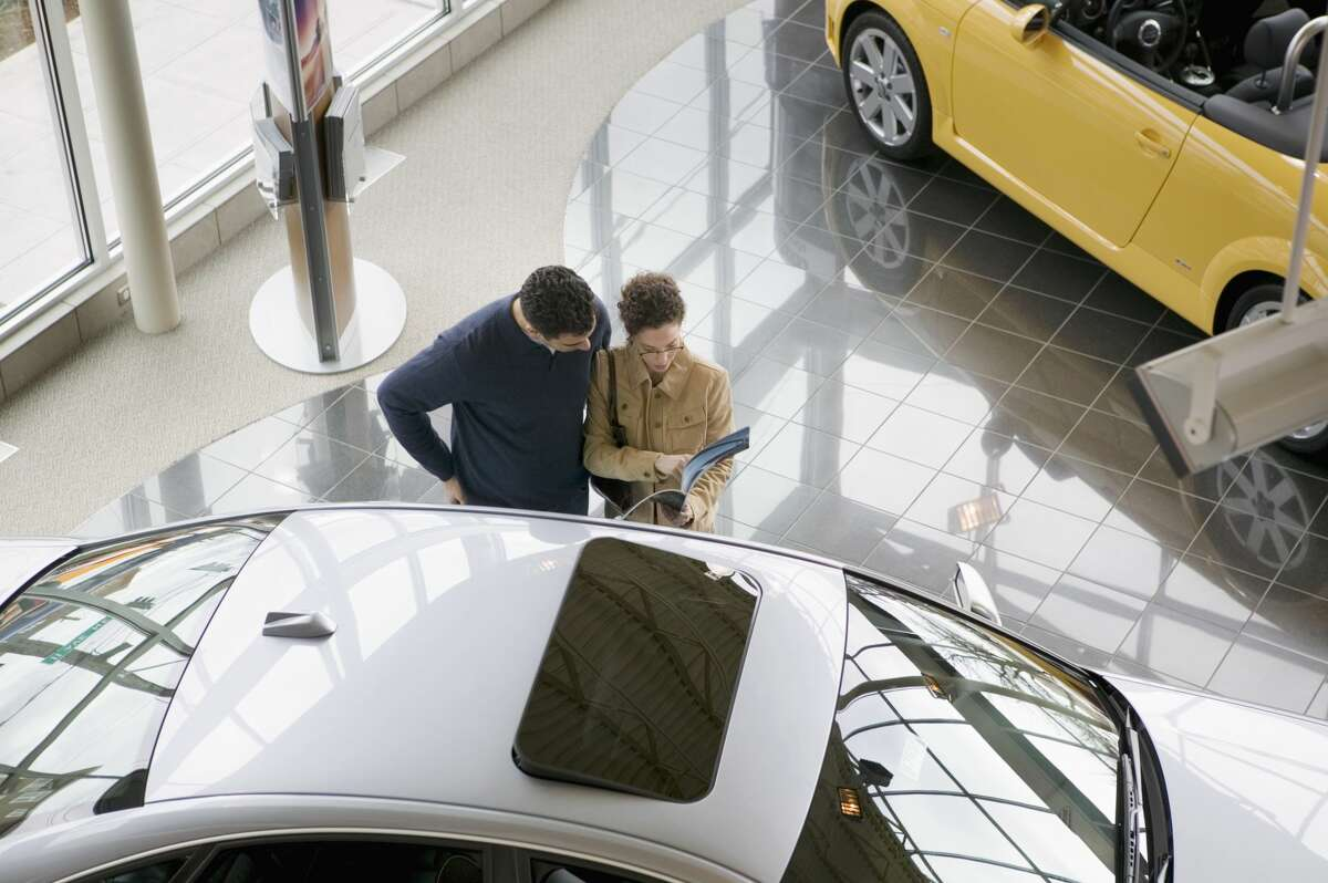Couple reading car information at a dealership